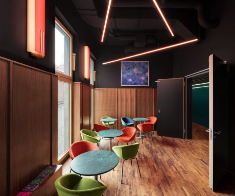 Delphi LUX, lounge, black ceiling, red led lights at the ceiling, old fashioned lamps at the wall, colored seats and tables, painting at the wall, Photo by Daniel Horn