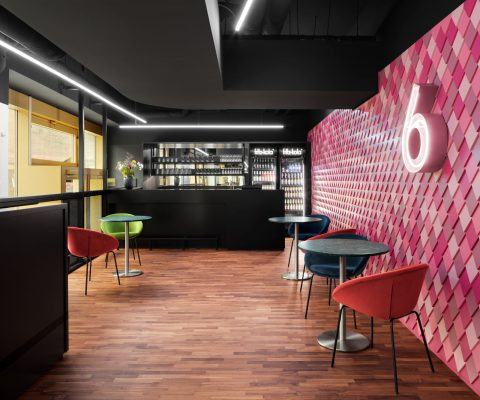 Delphi LUX, foyer in the rear of the cinema, entrance to theater 6 with design wall in pink and rose a illuminated 6, bar in the background, some colored chairs and tables, Photo by Daniel Horn