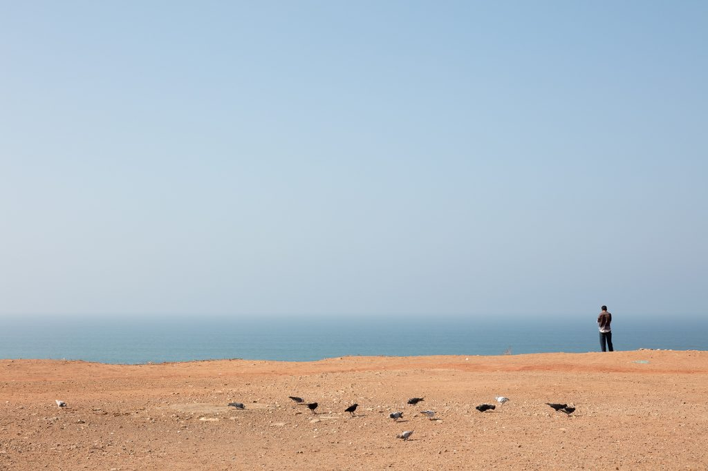 rabat, morocco, landscape format, red colored waste land close to the cliffs, some pigeons on the waste land, atlantic ocean in background, a man is standing close to the cliffs, blue sky, Photo by Daniel Horn