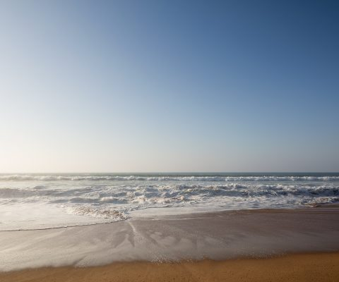 Plage des Nations, landscape format, beach near rabat morocco, sunset, waves on the red colored beach, blue sky, warm light, Photo by Daniel Horn